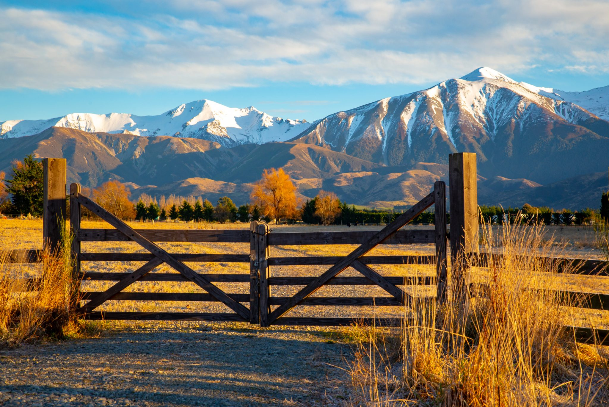 Picturesque snowy mountains behind a wooden farm gate.