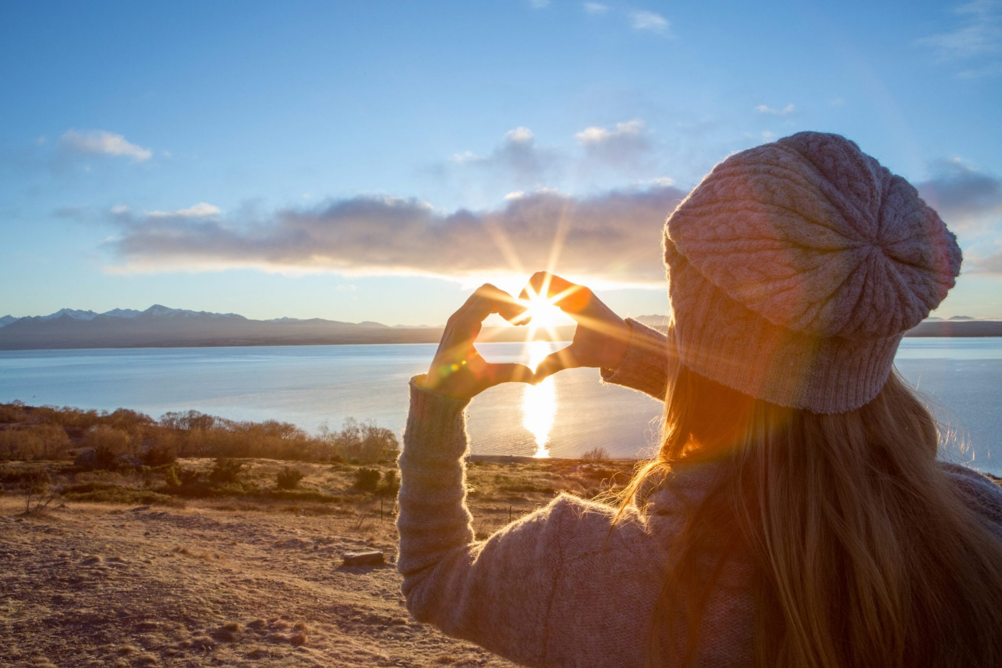 Young woman framing sunrise into heart shape finger frame
